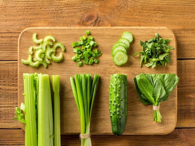비타민 샐러드에 대한 신선한 야채는 커팅 보드와 함께 나무 테이블에 놓여 있습니다. 개념. 평면도.