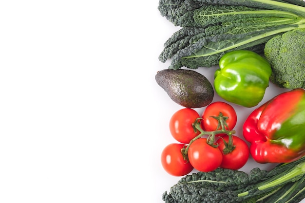 Fresh vegetables frame. black kale leaves, tomatoes branch, red and green bell pepper, avocado