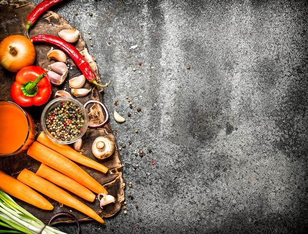 Свежие овощи. свежие овощи со специями, травами и морковным соком на деревенском столе.