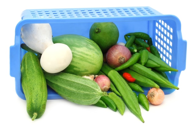 Fresh vegetables from a plastic basket over white background