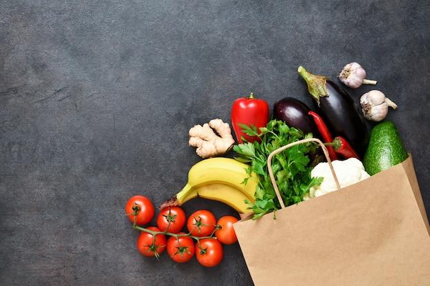 Свежие овощи, фрукты и зелень в хозяйственной сумке крафт-бумаги на черном деревенском фоне. эко-шоппинг и концепция доставки еды.