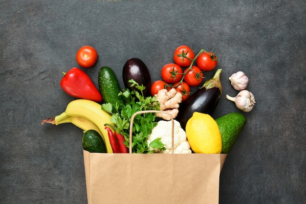 Fresh vegetables, fruit and greens in craft paper shopping bag on black rustic background. eco shopping and food delivery concept.