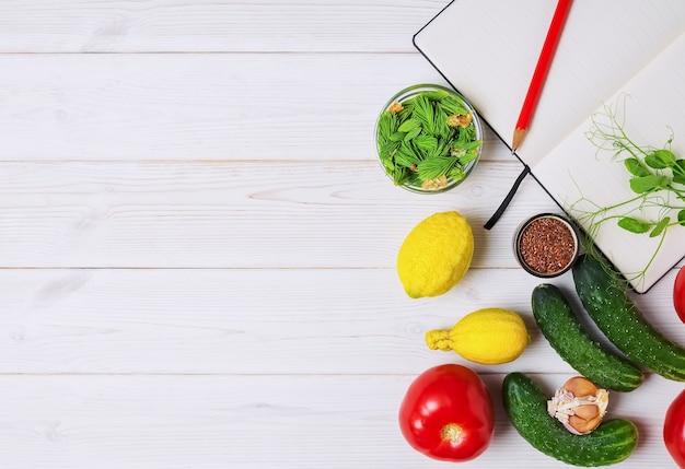 白いテーブルの上の開いた本と新鮮な野菜、果物、スパイス