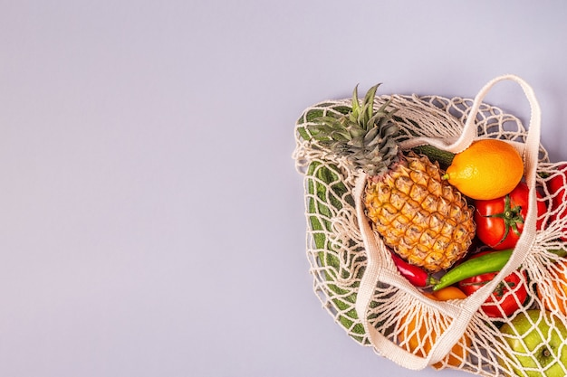 Fresh vegetables and fruits in bag mesh, top view.