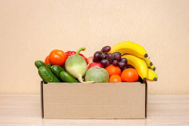 Fresh vegetables and fruits in a cardboard box on a wooden table