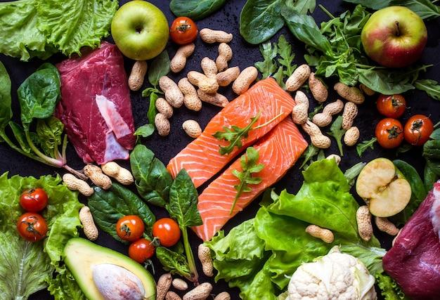 黒チョークボードの背景に新鮮な野菜、果物、魚、肉、ナッツ。