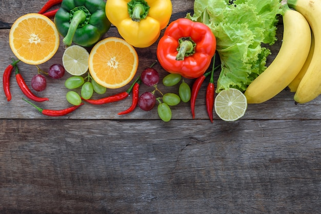 Fresh vegetables and fruits for fitness dinner on wooden background top view, food concept