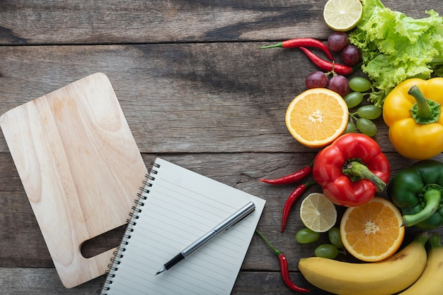 Fresh vegetables and fruits for fitness dinner on wooden background