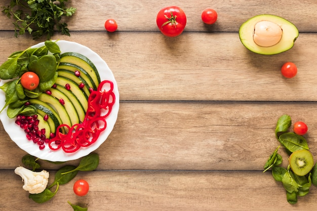 Fresh vegetables and fruits salad in white plate on wooden table