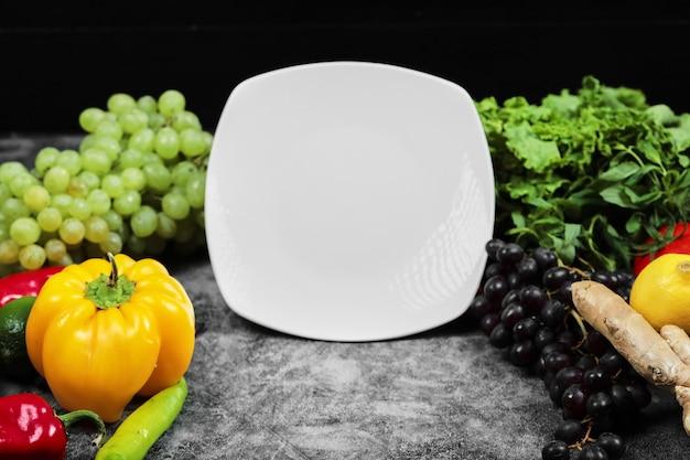 Verdure fresche, uva, peperoni, verde, limone, pomodoro e piatto bianco su sfondo scuro.