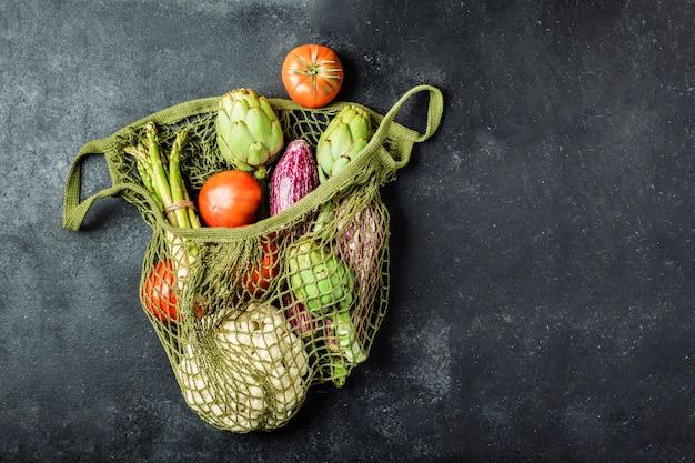 Fresh vegetables in a green string bag on a black table. cauliflower, tomatoes, artichokes, asparagus and zucchini.