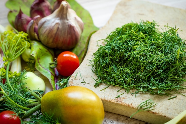 Fresh vegetables and greens on cutting board