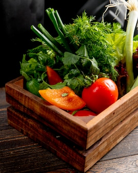Fresh vegetables and greens in wooden box