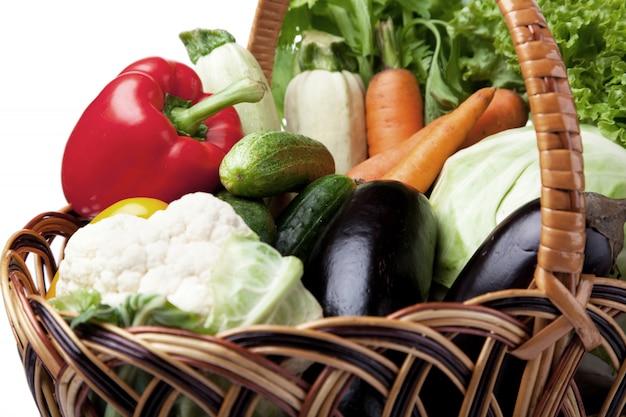 Свежие овощи в корзине на белизне.