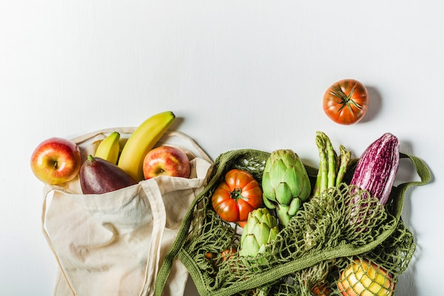 緑のひも袋に入れた新鮮な野菜と、天然素材で作った袋に入った果物。環境にやさしい商品です。プラスチックなし。