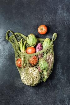 黒いテーブルの上の緑のひもバッグで新鮮な野菜。カリフラワー、トマト、アーティチョーク、アスパラガス、ズッキーニ。