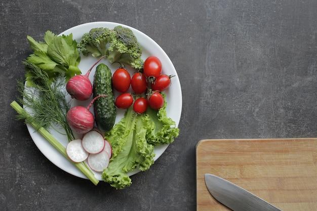 灰色のテーブルの上の白い皿に新鮮な野菜