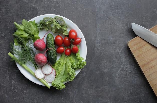 회색 테이블에 흰색 접시에 신선한 야채.