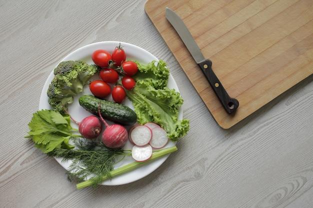 軽い木製のテーブルの白いプレートに新鮮な野菜