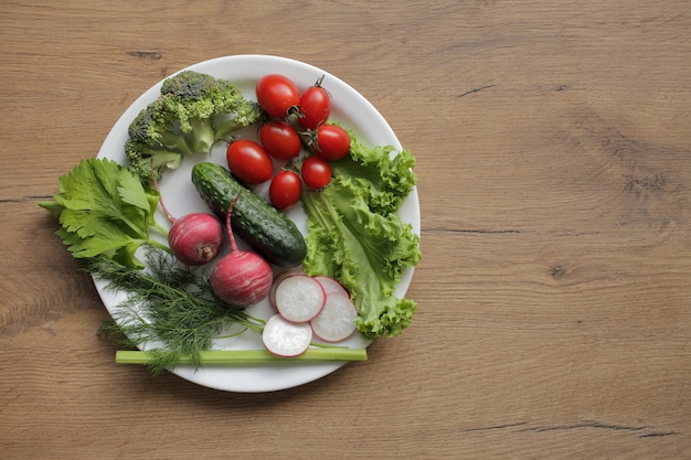 木製のテーブルの上の白い皿に新鮮な野菜