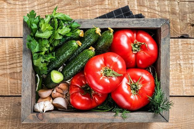 나무 상자에 든 신선한 야채, 빨간 토마토, 허브가 든 녹색 오이. 나무 배경입니다. 평면도.