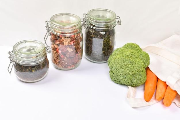 흰 벽에 친환경 베이지 색 토트 백에 신선한 야채. 제로 폐기물 개념. 드라이 상품이 담긴 유리 병