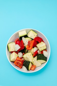Свежие овощи в кубиках в белой миске на синем фоне