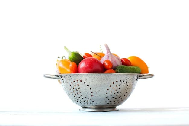 白の上の金属ザルの新鮮な野菜。健康的な食事。