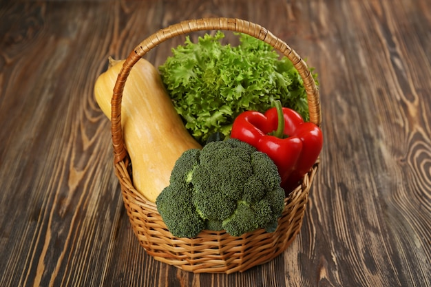 木製の背景に籐のバスケットに新鮮な野菜