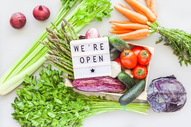 テキストと木製の箱で新鮮な野菜