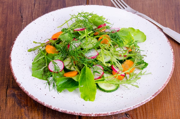 Fresh vegetables and leaves of green salads on white plate