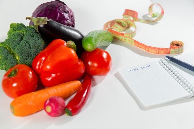 흰색 배경에 격리된 다이어트 계획이 있는 신선한 야채, 측정 테이프 및 노트북. 건강 식품 광고