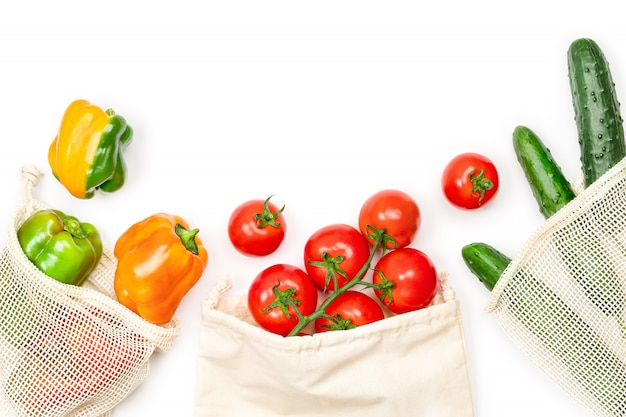 Fresh vegetables in mesh bag on white, top view. sustainable lifestyle.