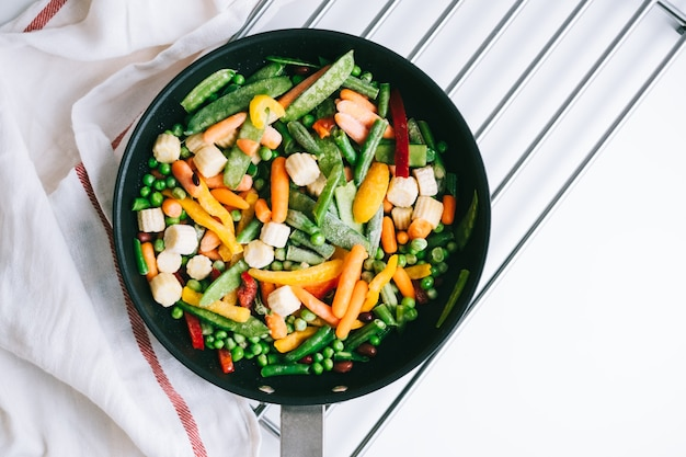 白いテーブルの上の黒い鍋に新鮮な野菜を混ぜます。健康食品