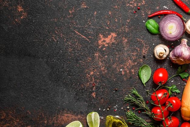 黒い石のテーブルに新鮮な野菜、キノコ、スパイス、ハーブ