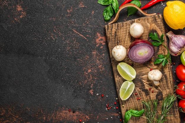 黒い石のテーブルの上のまな板に新鮮な野菜、キノコ、スパイス、ハーブ