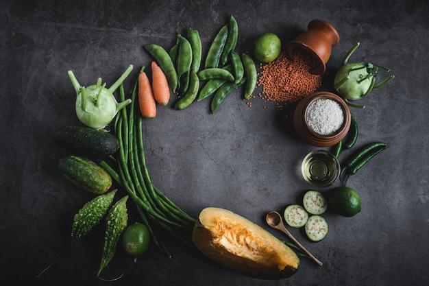 真ん中にテキストメッセージのためのスペースと黒いテーブルの上の新鮮な野菜