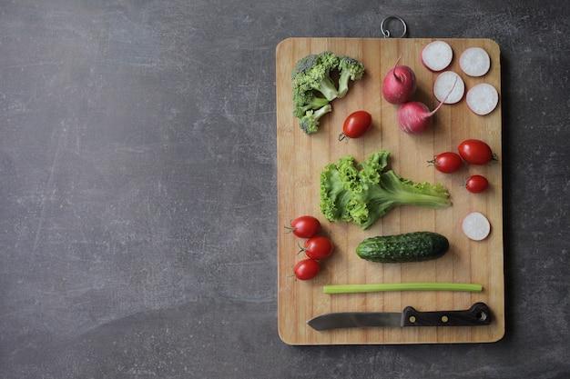 灰色のテーブルにまな板の上の新鮮な野菜