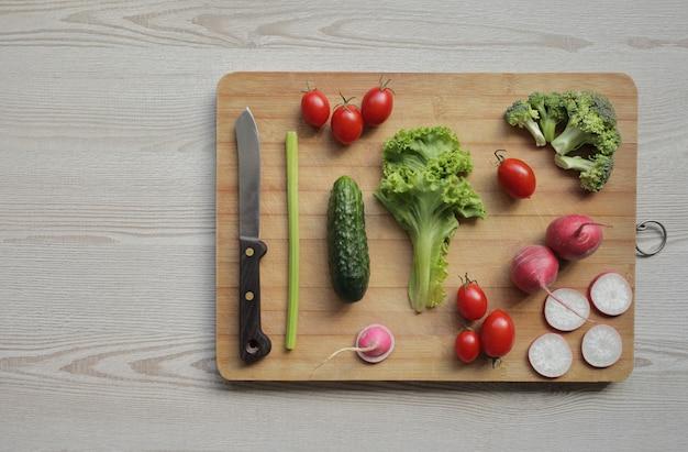 軽い木製のテーブルにまな板の上の新鮮な野菜