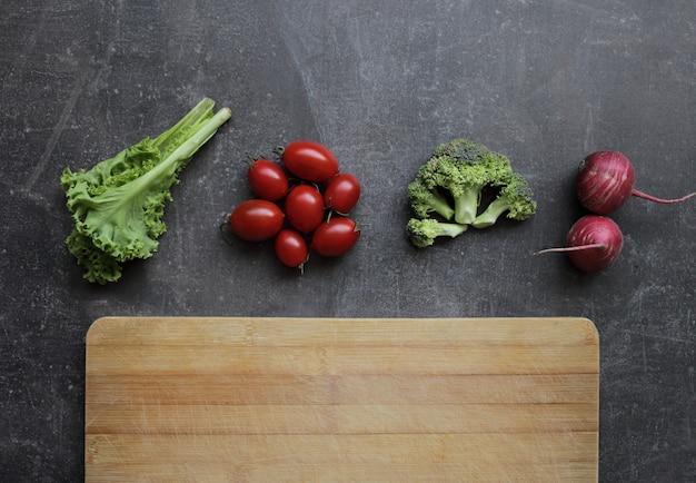 灰色のテーブルと木製のまな板で新鮮な野菜