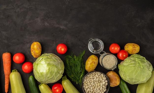 黒の背景に新鮮な野菜。有機食品のコンセプト