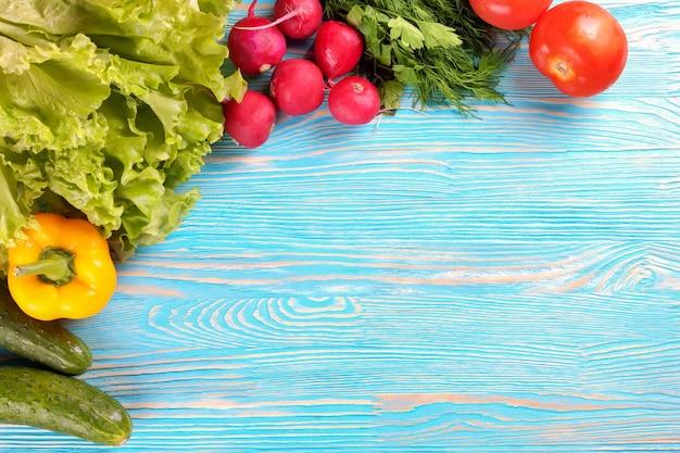 Свежие овощи на синем деревянном фоне. вид сверху.