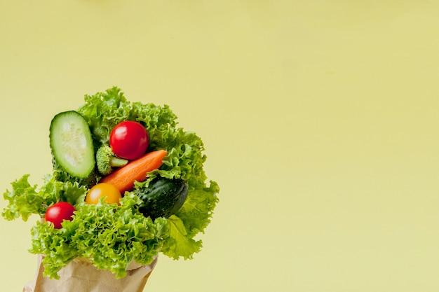 Свежие овощи на весах на желтом фоне. веганская и здоровая концепция.