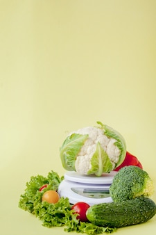 黄色の背景の花瓶に新鮮な野菜。健康的な食事、ダイエット計画、減量、デトックス、有機農業の概念。