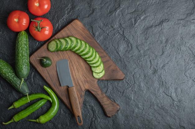 木の板に新鮮な野菜。トマトきゅうりとピーマン。高品質の写真