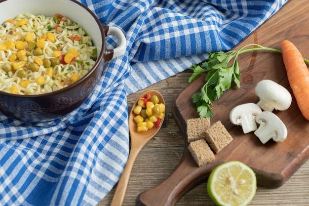 Свежие овощи на деревянной доске с лапшой