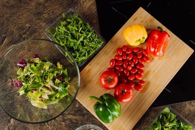 나무 절단 보드에 신선한 야채입니다. 토마토, 고추, rucola 재료 샐러드. 완전 채식 건강 식품 개념 및 평면도.