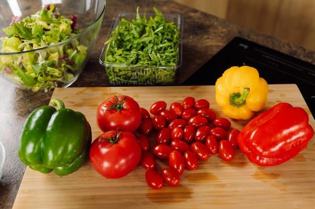 나무 절단 보드에 신선한 야채입니다. 토마토, 고추, rucola 재료 샐러드. 채식주의 건강 식품 개념. 상위 뷰 사진