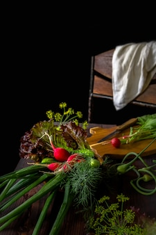 Fresh vegetables onion green feather radish on a dark wooden background in rustic style with copy space