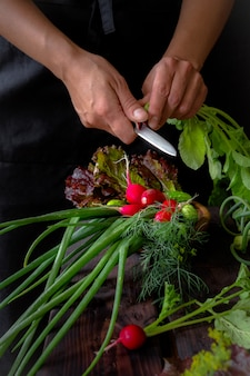 Fresh vegetables onion green feather radish and hands of the girl prepares on a dark wooden background in rustic style with copy space